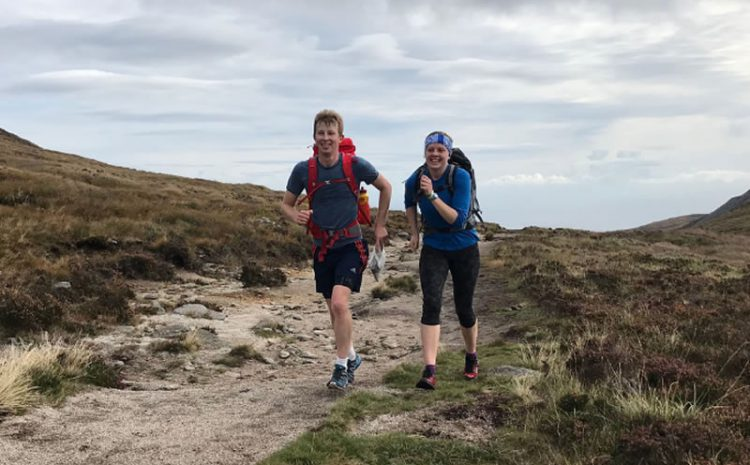 Two competitors running on rough path with grey sky