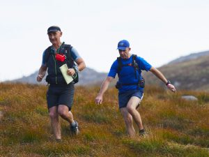Two competitors running across hills