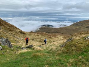 Two runners running in hills above mist