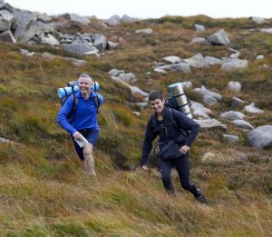 Two smiling runners out on hill