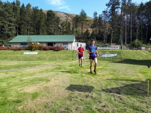 Two runners running towards day 1 finish