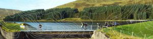 Competitors running across bridge in front of reservoir with contour lines