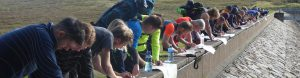 Competitors marking up maps on reservoir wall